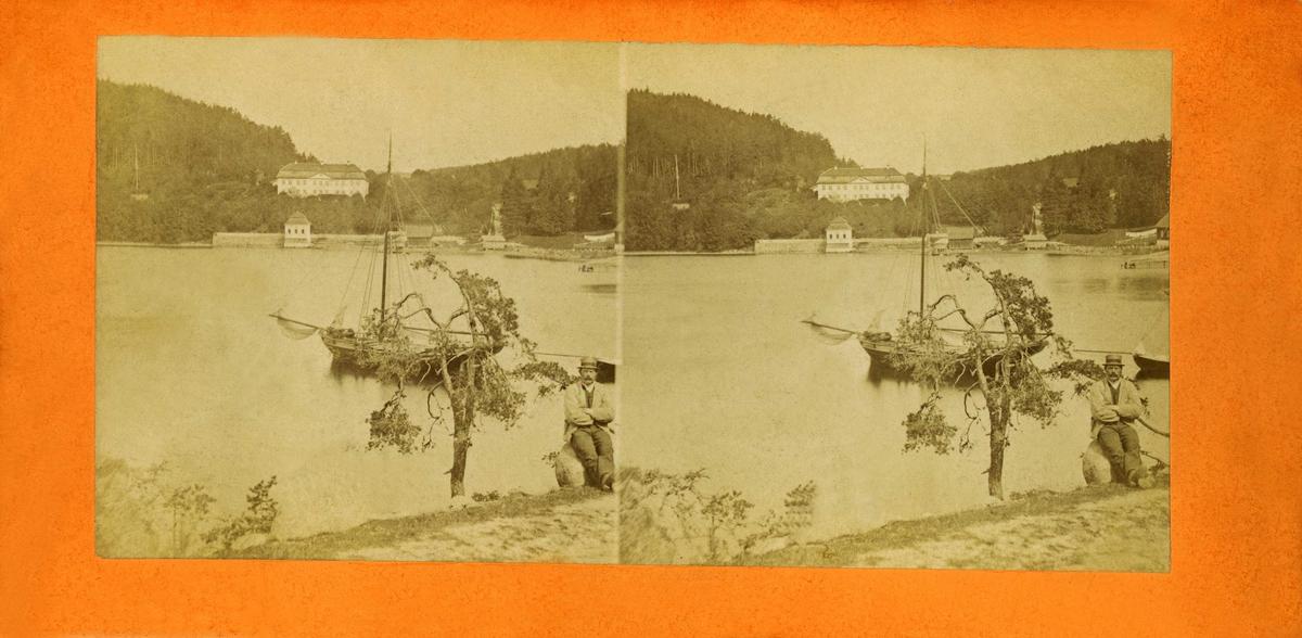 Godset Stubljan i Oslo som brant ned i 1913. Mann sitter ved sjøen i forgrunnen, og en seilskute ligger på fjorden. Stereoskopi.