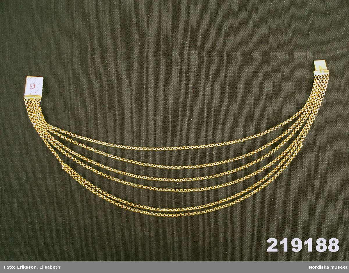 Halskedja av guld bestående av sex stycken kedjelänkar av ankartyp med cirkelrunda länkar. Rektangulärt lås av instickstyp med emaljmålning föreställande blomstermotiv i färgerna rött, vitt och svart mot blå botten. Vid låsets vardera sidor fem fasta öglor för kedjornas fäste. Låsets baksida försett med Kung Karl XI:ss namnschiffer. Enligt traditionen är smycket gåva av Karl XI till kyrkoherden Karsten Rönnow i Åhus, Skåne för att han vid ett tillfälle under det svensk-danska kriget 1676 - 1679 frälste konungens liv genom att gömma honom i en skorsten. /2008-01-16 Ingrid Roos Utdrag ur Kongl. Antiqvitets Archivets Inventarium år 1855: Inv.nr 21116.---Denna kedja--hade blifvit såld av någon Presten Rönnows ättling till en antiqvitetssamlare, Kopparslagaren Lang i Malmö, från hvilken den gått i arf till Kapten vid Kongl.Ingeniör Corpsen A.Wiggman, som sålde den till Museum för 167 Rd. 8 sk. B:co. Den betaltes efter 5 Rd. 32 sk. B:co lodet.