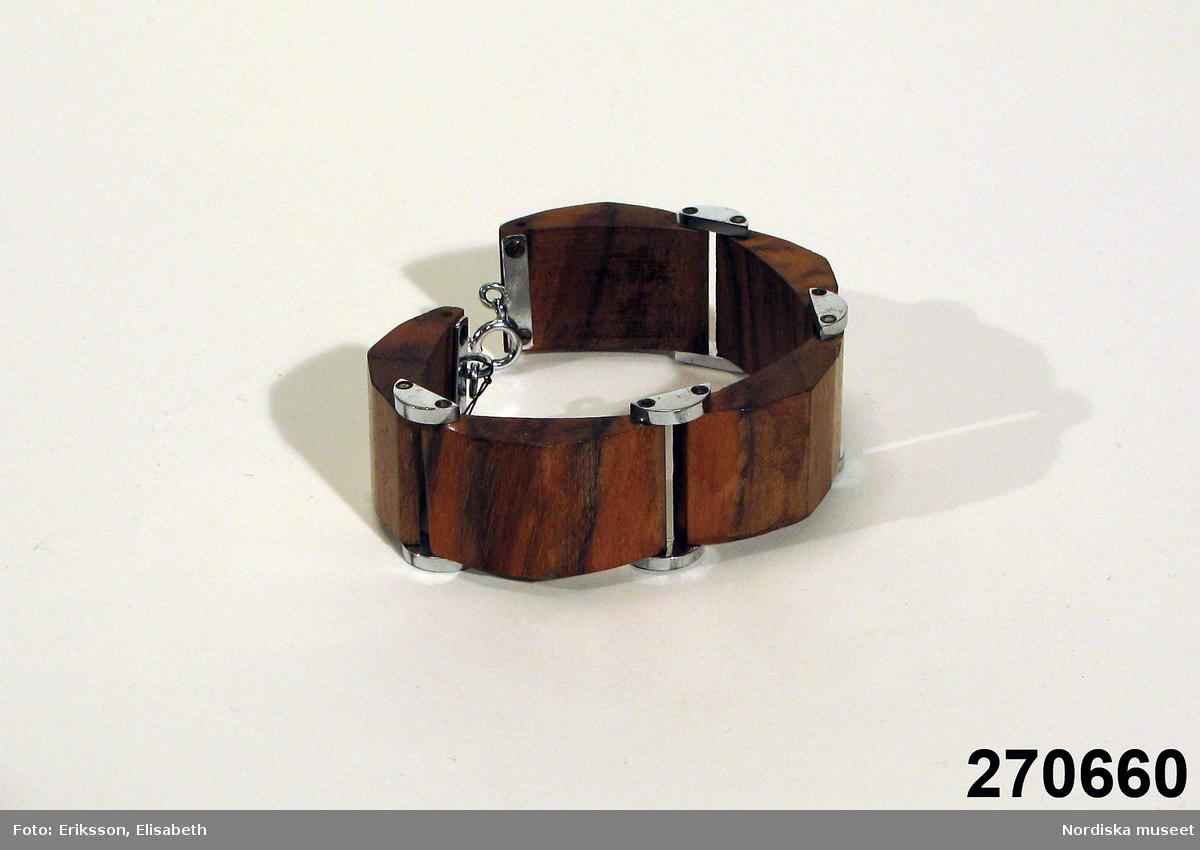 5 välvda bruna polerade träplattor ledade mot varandra med halvmånformade vitmetallbitar, låses med ringlås. Enligt uppgift köpt i Wien eller Tjeckoslovakien före 1930. /Berit Eldvik 2009-12-01