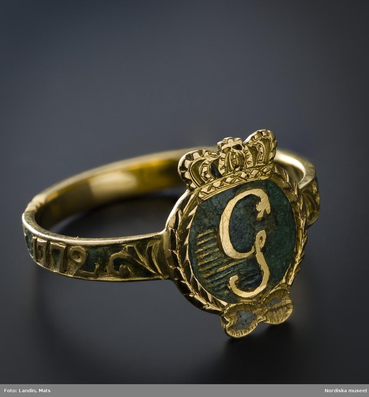 """Ring av rött guld,  med Gustav III:s monogram i guld mot grön emaljbotten, s.k. revolutionsring. Runt skenan graverad inskription """"den 19 aug 1772"""".   Den 19 augusti 1772 genomförde Gustav III sin statskupp. För att befästa sin ställning som landets reelle regent använde han sig av en för vår tid modern propagandaapparat. Kungen ville göra sig populär, göra PR för sig personligen och han insåg att folkets gunst skulle bli ovärderlig för honom. För att uppamma och hålla fast den måste undersåtarna ständigt ha för ögonen vad deras konung hade uträttat för att rädda landet från splittring, korruption och yttre fiender. Gustav III insåg souvenirens betydelse som instrument för detta. Souvenirer som hela tiden och i alla samhällsklasser skulle minna om den händelserika dagen. Sålunda skapades en serie minnesföremål som alla hade gemensamt att de bar konungens bild eller monogram samt revolutionsdagens datum. Eftersom dessa föremål har en tydlig social skiktning är det med största sannolikhet så att kungen ville nå ut till alla samhällsgrupper, inte minst ner till de lägsta klasserna. För den stora massan fanns billiga, lättåtkomliga kritpipor och för inflytelserika personer ringar, silverpjäser, dosor, hängsmycken, kinesiskt porslin, medaljer samt näsdukar.  Ringarna, som går under benämningen revolutionsringar finns i ett tiotal nu kända olika utföranden och av olika dyrbarhetsgrad. De flesta av ringarna bär texten """"den19 aug 1772"""", till minne av själva statskuppen. Några har endast texten """"den 21 aug 1772"""", dagen när  riksdagen antog den nya regeringsformen. Eftersom kungen hade vissa svårigheter att få igenom denna får man anta att ringar med detta senare datum gavs till vissa speciella personer, som stött kungen vid  just detta tillfälle. Av de olika souvenirerna är kritpiporna de mest spridda men också ringar av enklare utförande gjordes i stora mängder. Nordiska museet har i samlingarna en av de mer påkostade, en ring med kungens porträtt i guld mot blå emaljbotten"""