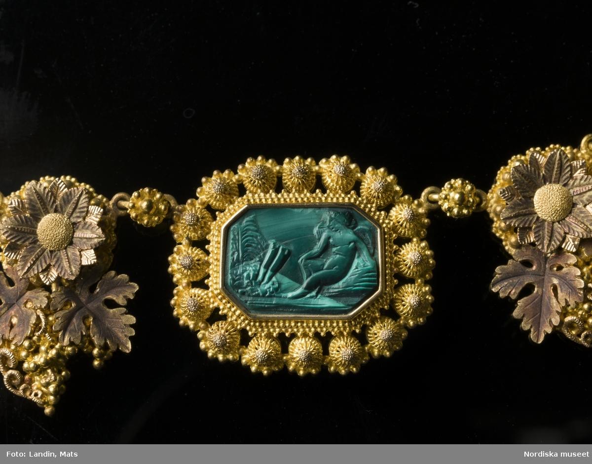 """Huvudliggaren: """"Smyckegarnityr af guld och malakit. Bestående af halsband, 2 armband, brosch, 1 par örhängen (ofullst.) diademkam i 2 delar och axelspänne. I rödt maroquinetui.  dep. 29/5 1914 Enkedrotttning Sophias sterbhus delegare.""""  a:1) Diadem, bredd 18,7 cm a:2) kam, bredd 14 cm, Höjd 8,5 cm b) Halsband, längd 44,5 cm c) Armband, längd 20 cm d) Armband, längd 20 cm e) Brosch, bredd 8,5 cm, höjd 9 cm f) Örhänge, längd 4,7 cm g) Örhänge (ofullständigt), längd 3,2 cm h) Axelspänne(?) i) Etui, bredd 31 cm, djup 23 cm, höjd 13,5 cm.  Smyckegarnityr av guld i fyra olika färger, s.k. """"quatre couleurs"""" och stenar av malakit med skurna reliefer med olika mytologiska motiv. Förebild  har bland annat varit Thorvaldsens """"Dagen"""",   Malakit var fram till viktoriansk tid en sten som användes i exklusiva smycken. senare Den förlorade sedan i status och kom då till användning i inte fullt så dyrbara smycken."""