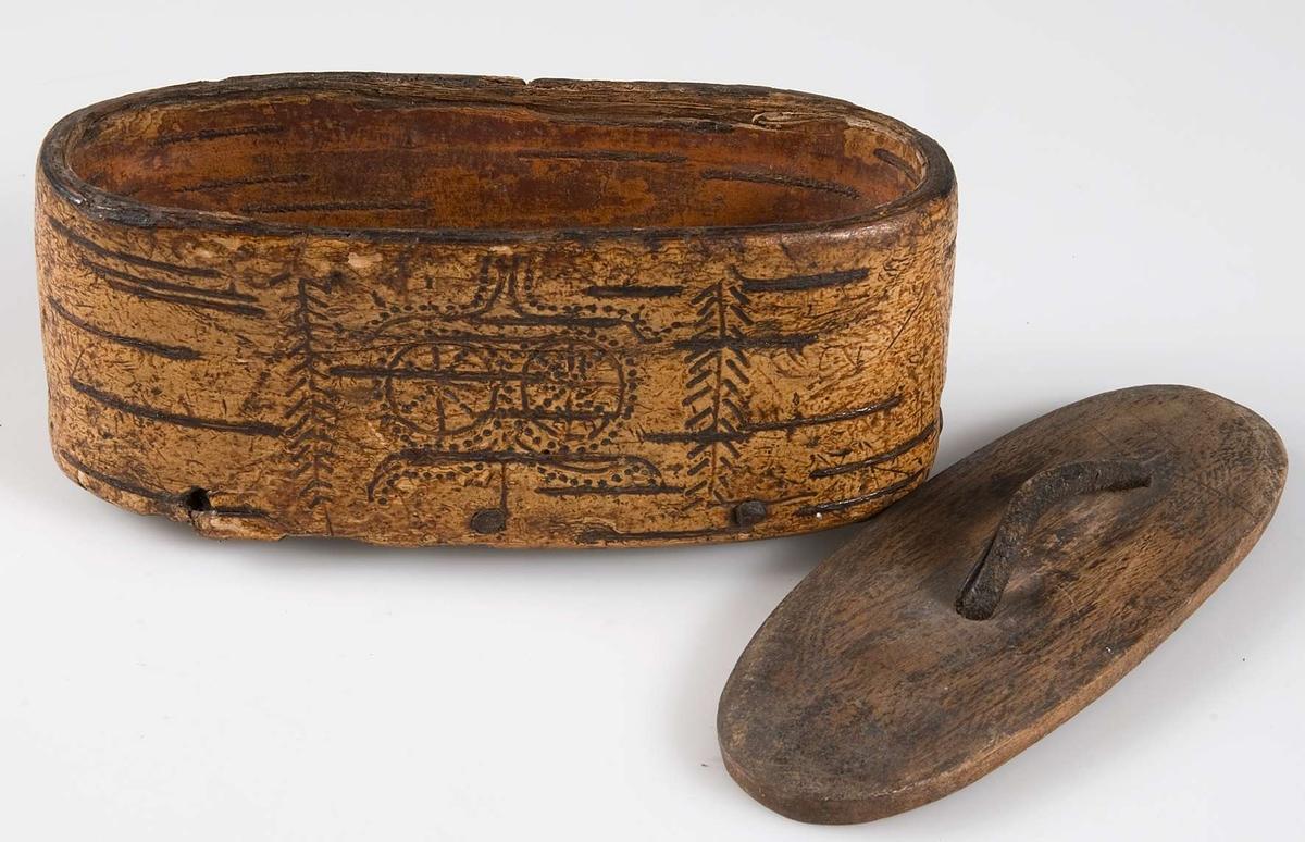 Snusdosa av näver. Brännornamentering. Botten och lock av trä. I botten inristat: ITEIB. Läderhandtag.