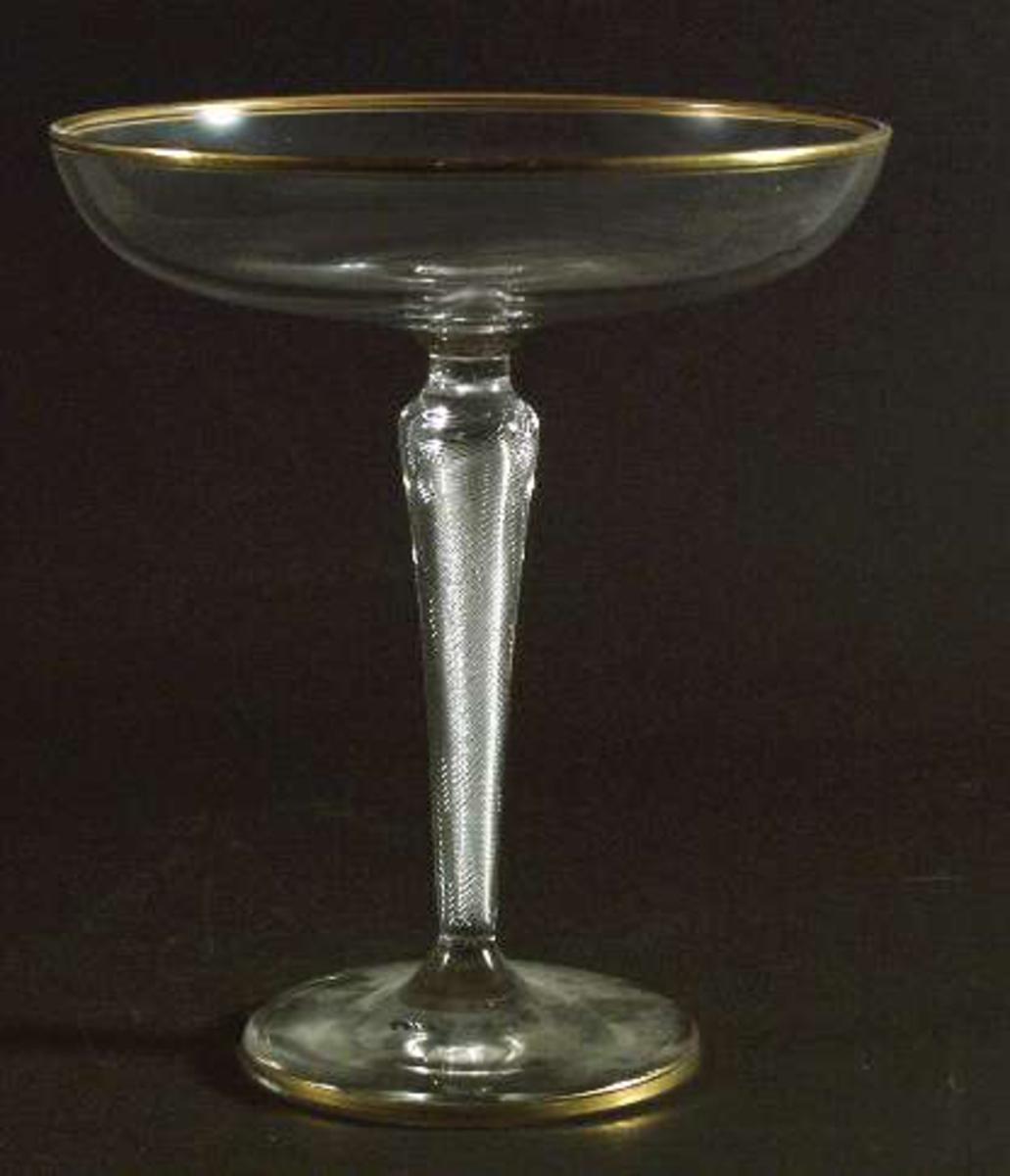 Konfektskål av ofärgat glas. Luftspiral i benet. Guldband kring mynning och fotplatta.