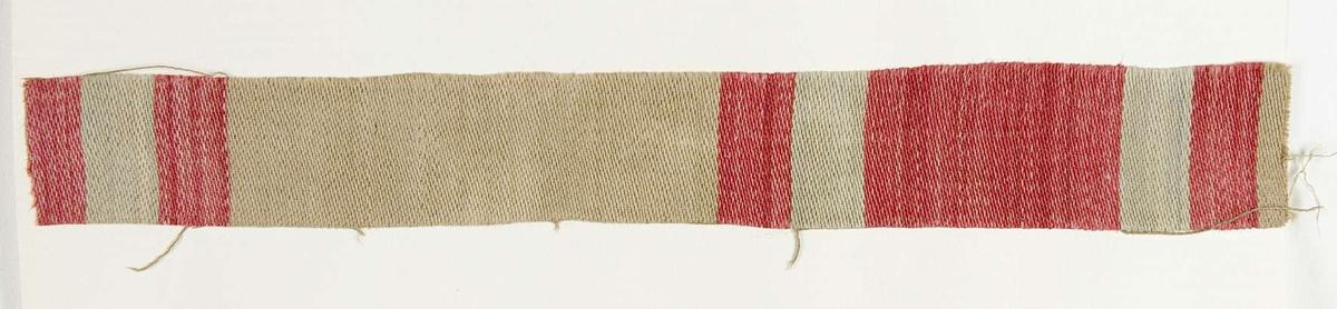 """Vävprov ämnat för bolstervarstyg vävt med bomullsgarn, satinbindning. Randigt i beige och rött. Vävprovet är uppklistrat på en kartong i storleken 22 x 28 cm. I övre högra hörnet finns en stämpel """"Uppsala läns hemslöjdsförening"""" och ett handskrivet nummer, """"A.1635""""."""