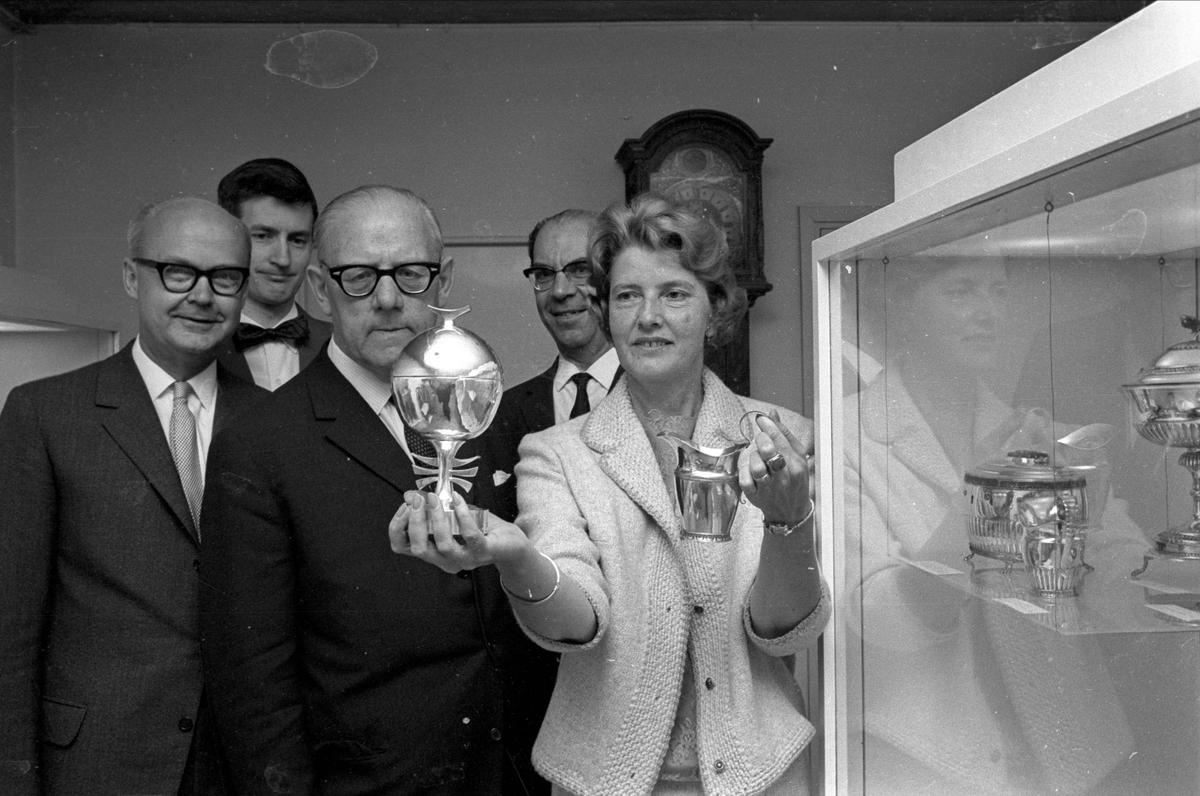 Anna-Märta Berg håller i en gräddkanna och en bonbonniere som Upplandsmuseets vänner skänkte till Upplandsmuseet, Uppsala 1966