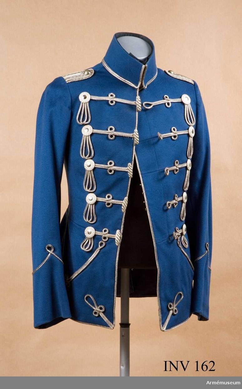 """Stl B 46. Motsvarar i utseende en svensk dolma för officer i  snittet. Av mellanblått kläde med silversnörmakerier.  Ståndkrage m/1895, rakskuren, med nertill rundade hörn, ihophäktad med 3 st häktor. Kragen är fodrad med kläde, med  klaff fodrad med svart satin. Attilan knäpps med 5 st öglor av  galon och """"pinnar"""" av silvermetall = snörmakeri. På avigsidan  är plagget ihopfästat med 2 st spänntampar med platt metallspänne. Även ihophäktad med 5 st häktor. Skört 230 mm  högt, med snedställd, nägot ringad ficka, en st på vardera  framvåden. Skörten bak är utställda 40 mm och vid midjesömmen  går de 40 mm omlott. En ficka fodrad med vit lärft innanför  varje flik. Ärmen med uppslag och snörmakeri. Uppslagets höjd  130-170 mm.  Källa: Formations und Uniformierungsgeschichte  1808-1814, band  II, AM bibliotek."""
