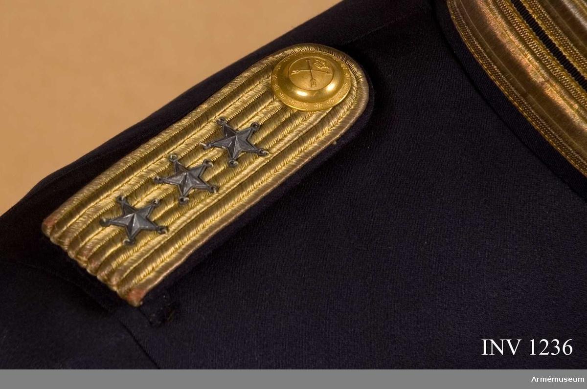 Till vapenrock, med foder av blått kläde. Framsidan klädd med beläggningssnören i guld. På beläggningssnöret är tre stjärnor fästade=kaptens grad och en knapp m/1754 i reg:s m/större. Baksidan försedd med en slejf av kläde och en hake i gulmetall avsedd att fästas i rockens två hällor på axeln.