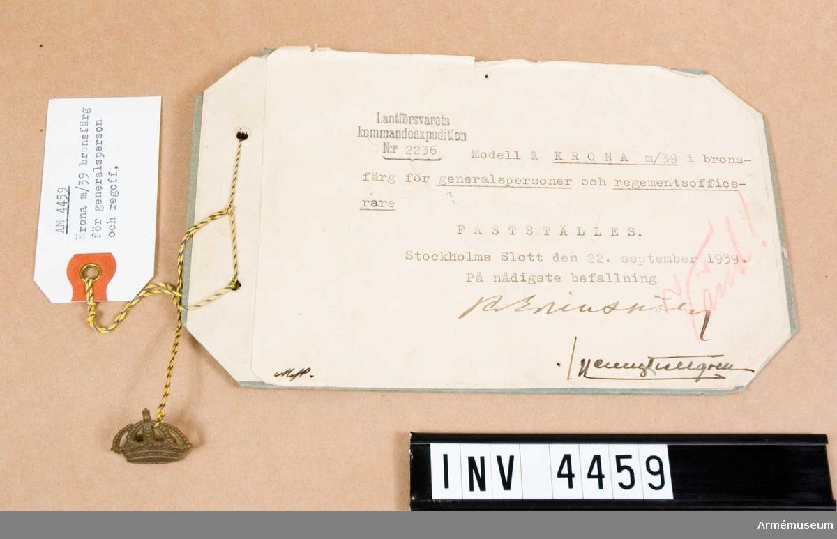 """Gradbeteckning m/1939, generalsperson/regementsofficer.Av metall. Anbringades på krage vapenrock/kappa ovanför truppslags- eller personlakårstecken medelst två klammer, fastlödda på baksidan. Vidhängande etikett anger fastställelsedag: """"Stockholm Slott den 22. sept. 1939 Per Edvin Sköld /Henry Kellgren"""".Den 4 apr 1941 fastställdes f genpers eklövsemblem m/1939, bronsfärg i broderat utförande. Anbringas på kragen på vapenrock/kappa i stället f krona m/39 och personalkårstecken, varför krona m/39 endast kom att anläggas av regoff."""