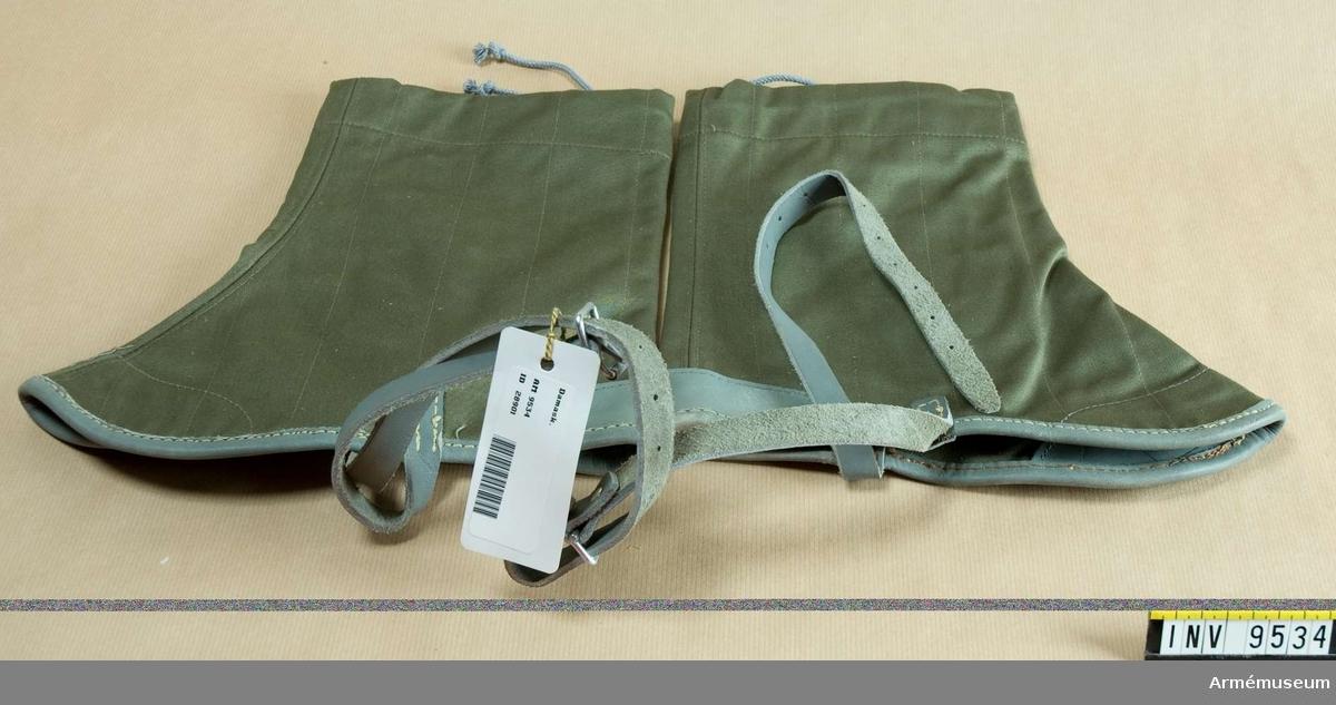 Båda damaskerna stämplade Haeren 9885. Är tillverkade av grönt tyg och är försedda med läderskoningar vid häl och tår. Har rem under foten och är försedda med snodd upptill för åtdragning. Gåva från FMV.