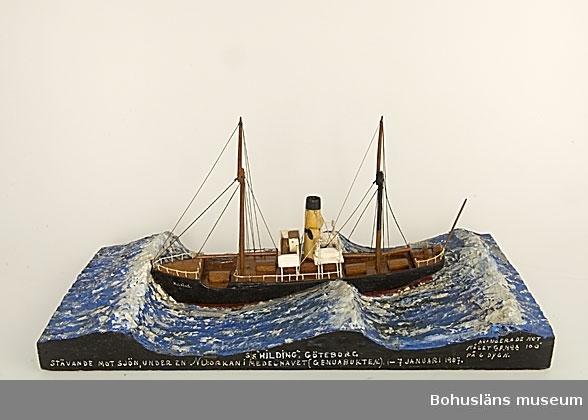 """Fartyget """"Hilding"""" monterad på en rektangulär träplatta med modellerat hav. Text på ena långsidan: S/S """"HILDING"""". GÖTEBORG STÄVANDE MOT SJÖN, UNDER EN NO:ORKAN I MEDELHAVET (GENUABUKTEN.) 1-7 JANUARI 1907. AVANSERADE MOT MÅLET GENUA PÅ 6 DYGN Historik se UM 5807.  Ur handskrivna katalogen 1957-1958: """"SS Hilding"""" Modell på platta. L. (från för till akter) 32. Föremålet helt. Från kapten Olssons saml., Fiskebäckskil."""