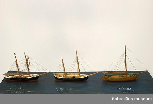 """Tre fartygsmodeller, skonerten Hjalmar, galeasen Hamlet och jakten Örnen från Fiskebäckskil. Tillverkade av kapten John Emil Olsson (1880-1950), Fiskebäckskil på Skaftö i Lysekils kommun på 1940-talet. Trä, metall, lintråd. Jakten - höjd 20 cm, längd 24 cm, bredd 4,5 cm; platta 79 x 22 cm; okänd skala. Vattenlinjemodeller med stående och löpande rigg, däckshus och lastluckor.  Skonerten och galeasen med svartmålade skrov och röd bottenmålning, jakten med gulmålat skrov och röd bottenmålning. Monterade på utskuren blåmålad platta. Ovanpå  plattan står textat med vita tryckbokstäver från vänster till höger:  SKONERT """"HJALMAR"""" BEFÄLHAVARE. SJÖKAPTEN. ANTON KRISTENSSON. F.B.KIL GALEAS """"HAMLET"""" BEFÄLHAVARE. C.M. JOHANSSON. F.B.KIL. JAKT """"ÖRNEN"""" BEFÄLHAVARE ANDERS MARTINSSON. F.B.KIL.  Definitioner: Skonert Ett segelfartyg med två eller fler master av vilka den förligaste har fullständig råsegeltackling och övriga gaffelsegel med trekant-toppsegel. Råsegel - rektangulärt eller trapetsformigt segel som förs på en rå, dvs. en horisontell stång fäst vid mastens framkant Gaffelsegel - trapetsformat segel fäst längs akterkanten av masten och med sina övre (kortare) och undre (längre) lik (kanter) fäst vid två rundhult (gaffel resp. bom).  Galeas Ett mindre, tvåmastat segelfartyg riggat med gaffelsegel som skonare med stormasten främst.  Gaffelsegel - trapetsformat segel fäst längs akterkanten av masten och med sina övre (kortare) och undre (längre) lik (kanter) fäst vid två rundhult (gaffel resp. bom).  Jakt Enmastat segelfartyg med öppet däck och en mindre kajuta akterut.  Gaffelsegel - trapetsformat segel fäst längs akterkanten av masten och med sina övre (kortare) och undre (längre) lik (kanter) fäst vid två rundhult (gaffel resp. bom).  Ur handskrivna katalogen 1957-1958: """"Hjalmar"""", """"Galeas"""", """"Hamlet"""" Skonerten Hjalmar, Galeasen Hamlet, Jakten Örnen. Modell på platta. Plattans mått 78,5 x 22,5. Föremålen hela. Från kapten Olssons saml., Fiskebäckskil.  För ytterligare info"""