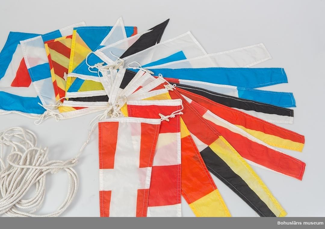 Del av internationellt signalställ på lina med 18 sydda flaggor i polyester. Flaggorna är 35x24 cm ca, rektangulära och trekantikga, inbördes kopplingsbara med knappar av plast. Detta flaggställ använt vid festliga tillfällen för utsmyckning ombord.