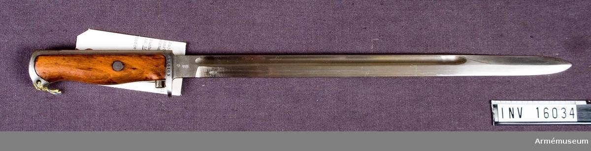 Klingans bredd vid fästet: 20 mm. Bajonetten är smidd i ett stycke och har eneggad klinga med en blodränna. Grepplattorna av trä fastsatta med skruv. Låsknappen är placerad omedelbart ovanför parerstången och står i förbindelse med spärren i grepphuvudet via en stång som löper diagonalt genom greppet. Märkt med Kongsbergs stämpel.Tillv.nr: 126105.  Samhörande: AM 16034 bajonett m/1912. AM 16035 balja till bajonett m/1912.