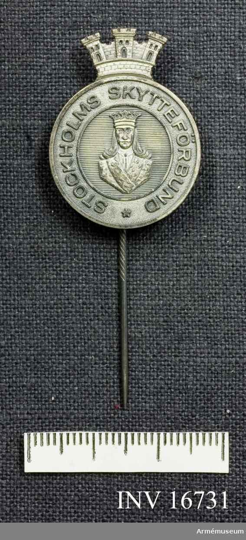 Stockholms skytteförbund. Ett försilvrat märke med S:t Eriks bild i mitten och krönt med  tre torn. Det är Stockholms vapen känt från 1326. Runt kanten står det: Stockholms skytteförbund. Baksidan bär tillverkningsstämpel från Sporrong.  Samhörande nr är AM.16715-16732