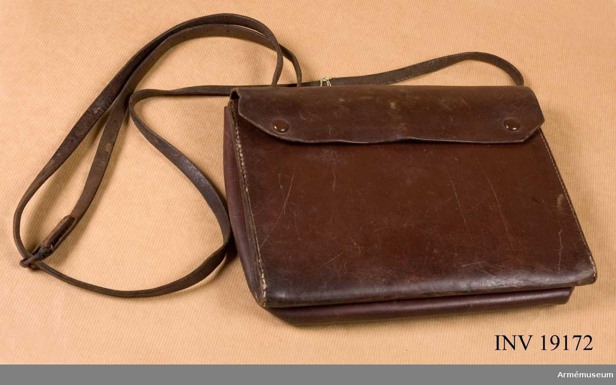 Samhörande nr är: 19161-76, rockar, kappa, m m personlig utr. Rapportväska m/1898. Av brunt läder med lock knäppt med två tryckknappar. Försedd med kartfodral och fack för linjaler och pennor. På baksidan ringar för axelremmen.