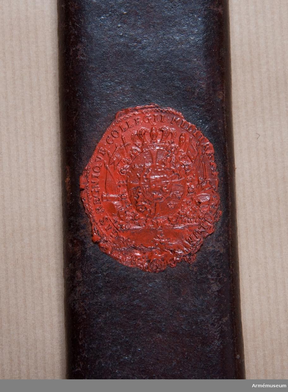 Grupp D II.  Baljan är klädd med ursprungligen brunt läder. Den har munbleck, mittbeslag och släpsko av mässing. Öglorna för koppelringarna sitter ej på beslagens ryggar utan vid kanten åt utsidan.På munbleckets ögla är siffran 4 inslagen. Mittbeslaget och ringöglorna har vid båda ändar, munblecket längs sin nedre och släpskon längs sin övre kant en ingraverad rand, varjämte alla ovannämnda kanter på munbleck, mittbeslag och släpsko pryds av två utbuktningar och en mellan dessa inskjutande flik. Längs den nedre och en del av den främre kanten är släpskon skodd med stål. På baljans utsida finns spår av en påklistrad papperslapp och dessutom krigskollegii sigill i rött lack