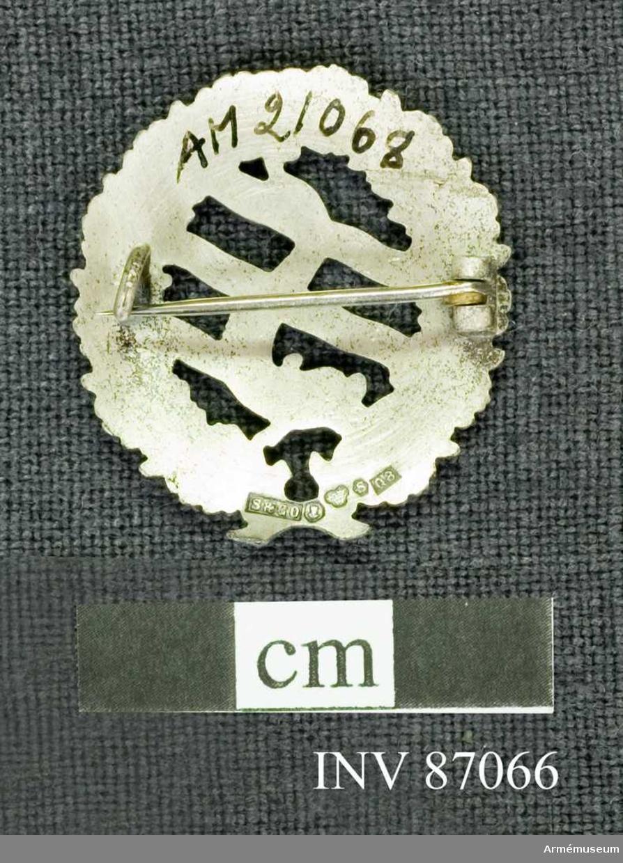 Grupp M.  Materialet är silver, vilket framgår av den på frånsidan befintliga kontrollstämpeln och arsbokstaven O 8.  Prn.