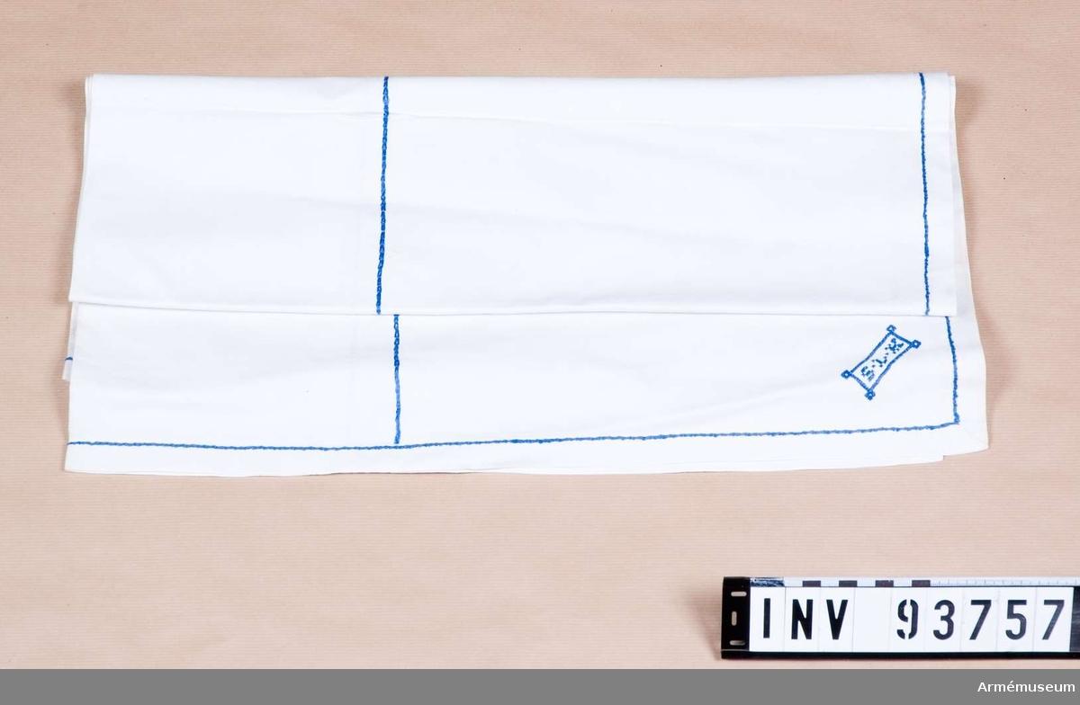 Vit duk med enkla blå broderier samt märkning broderad i ena hörnet.