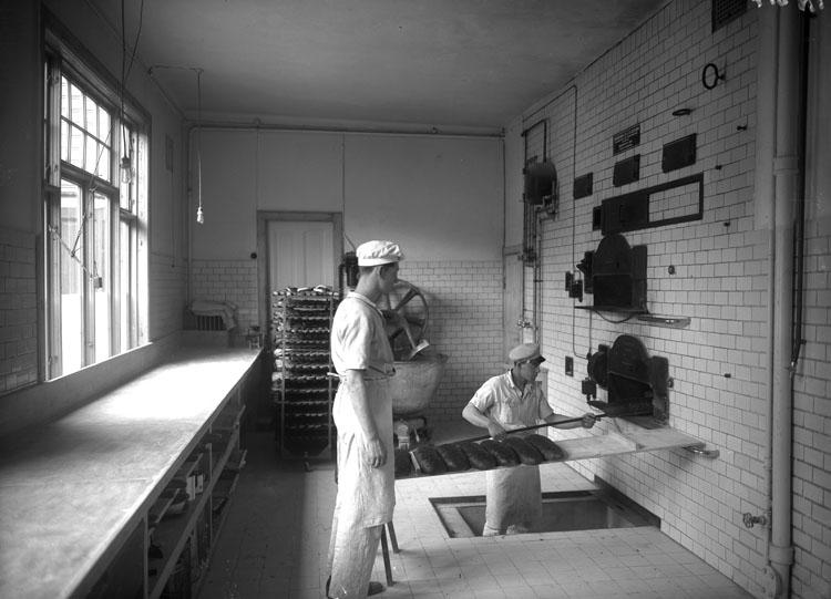 """Enligt tidigare noteringar: """"Interiör från S.E. Hennings bageri, Kämpegatan 2 Uddevalla. Bagaren vid ugn i gropen är Folke Johansson, den andre Karl Ek"""""""