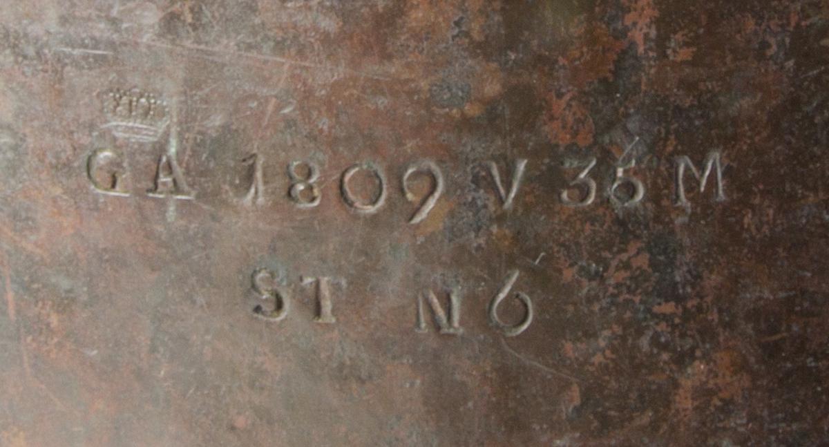 Kopparflaska, större cylinderformad med rak pip. Två nitade runda handtag upptill. Mindre lock som är fäst vid flaskan med kedja. Märkt med G A 1809 V 35 M, under detta ST N 6.