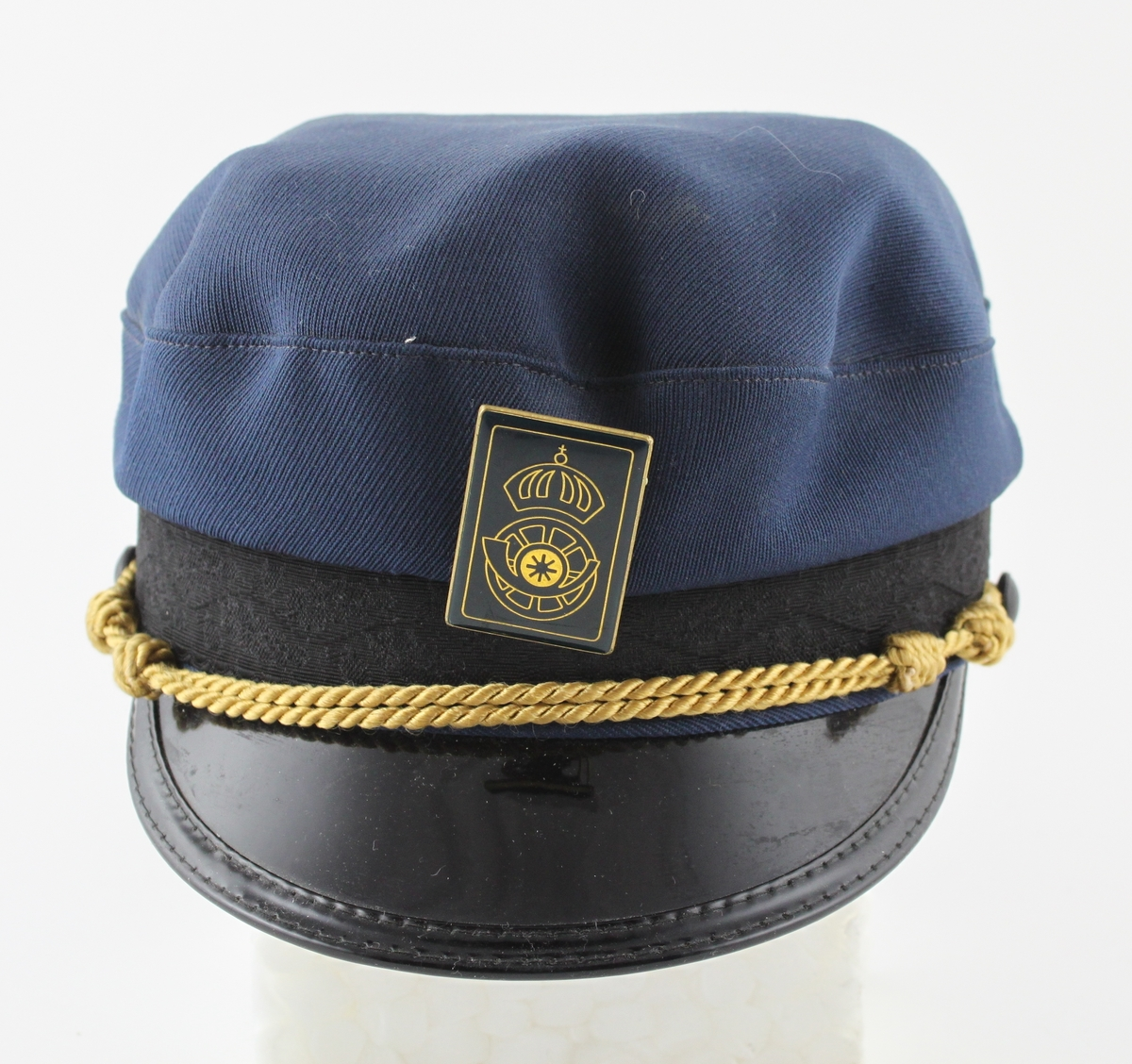 Uniformsmössa i blått ylle med mörkblått mössband och svartlackerad kantad skärm. Mössnodd i gul träns. Rektangulärt mössmärkemed Postens Diligenstrafiks symbol.