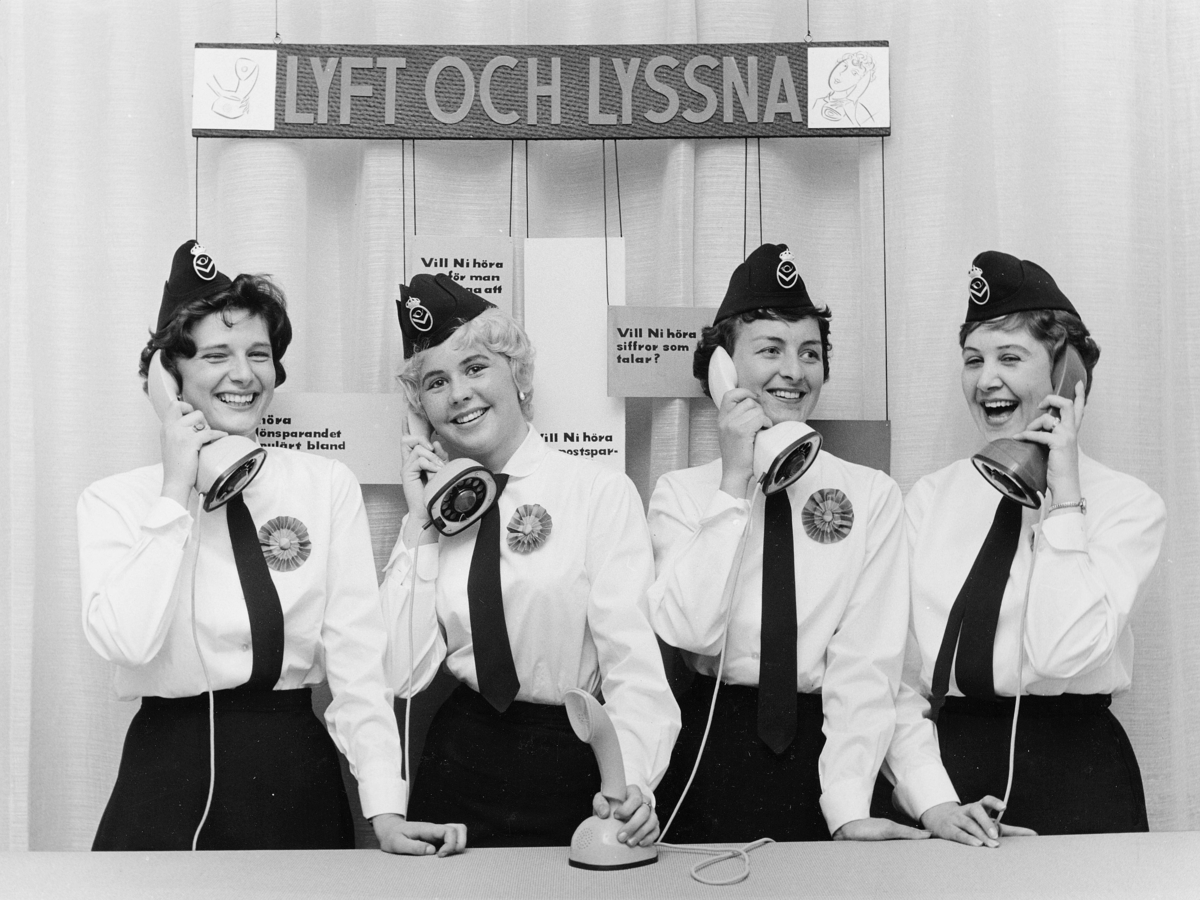 Fyra sparvärdinnor i nya uniformer lyssnar i LM:s eleganta ericofoner.