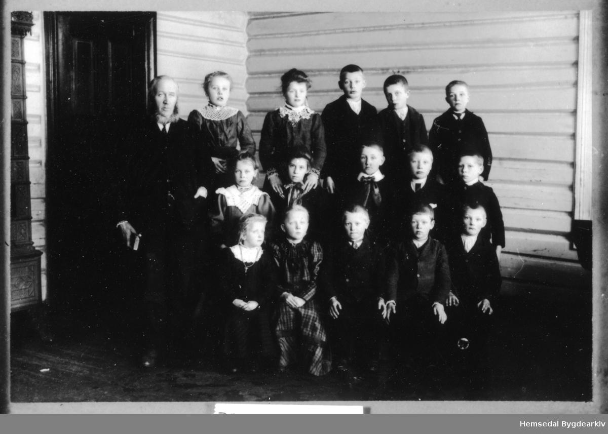 """1.-4. klasse ved Trøym skule i Hemsedal ved skulestart 1910-1911. Skulen låg den gongen i det gamle heradshuset som låg i same området som bilioteket/Kyrkjestugu i dag (2013). Det gamle heradshuset vart rive kring 1980. Læraren er Odd S. Grøthe (""""Klukkaren""""). Fyrste rekke frå venstre: Ingrid K. Trøym, Liv O. Jordheim, Trond Haug, Andres Trøym, Knut J. Grøthe. Andre rekke frå venstre: Margit O. Nygard, Margrethe Snikkarbråten, Olav Jordheim (Nilsongard), Knut O. Flaget, Ingvar Sletto. Tredje rekke frå venstre: Birgit S. Kirkebøen, Karoline Kveen, Eirik J. Grøthe, Jakob Haugen, Ola N. Fekene."""