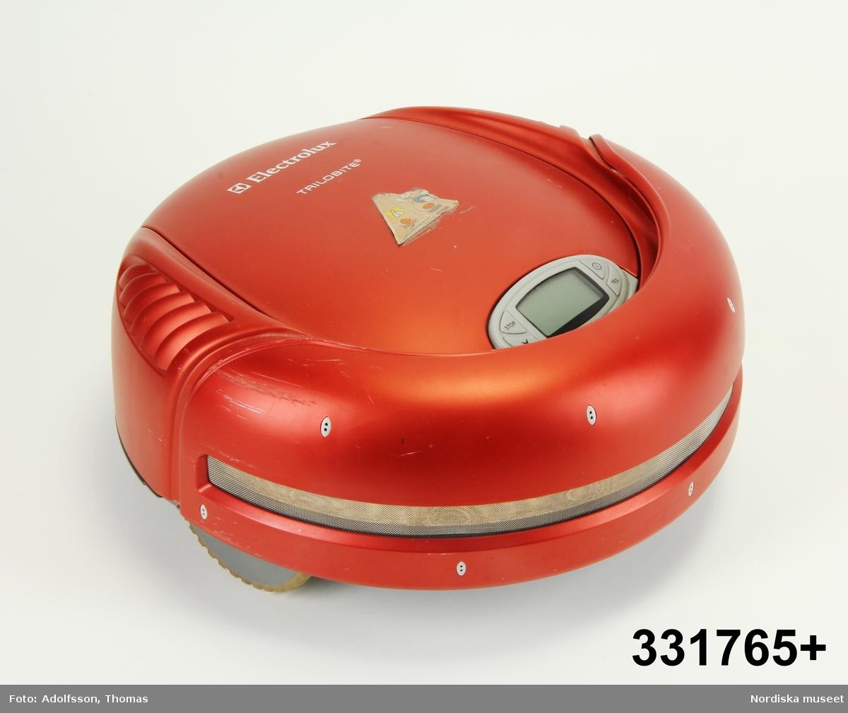 """Automatisk hushållsdammsugare, så kallad """"robotdammsugare"""" av märket Electrolux Trilobite. Dammsugaren är en låg cylinder med avrundade kanter upptill, rödfärgad. På ovansidan display, filterlucka och integrerat handtag. På filterluckan ett klistermärke som varnar för att dammsugaren kan trilla nedför trappor om dess framfart inte stoppas genom montering av magnetlister.   Undertill två drivhjul och en borstvals. Mitt på cylinderns baksida kontaktbleck för anslutning till den medföljande fristående batteriladdaren (inmärkt separat). Efter städning återvänder dammsugaren till laddaren där dess batteri laddas elektriskt.  Anm. några repor på skalet.    /Maria Maxén 2013-08-12"""