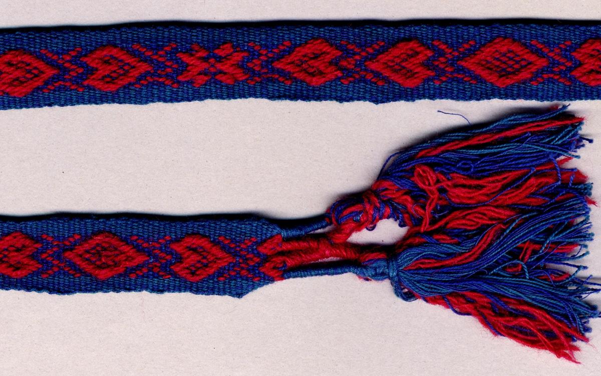 Förklädesband med plockat krabbasnårsmönster. Blått och blågrönt bomullsgarn i botten med mönster i rött ullgarn. Mönstrat med hjärtan, stjärnor och snedrutor. Avslutat i var ände med två tofsar, varptrådarna är först omlindade med blått och rött garn vari extra trådar i samma färger till tofsen är iknutna (Lindning: 25 mm lång, tofs: 70 mm lång).Varp i blått och blågrönt 2-trådigt s-tvinnat bomullsgarn och rött 2-trådigt s-tvinnat ullgarn. Inslag i blått och blågrönt 2-trådigt s-tvinnat bomullsgarn, två trådar tillsammans; en tråd av varje färg. Längd inklusive tofsar.