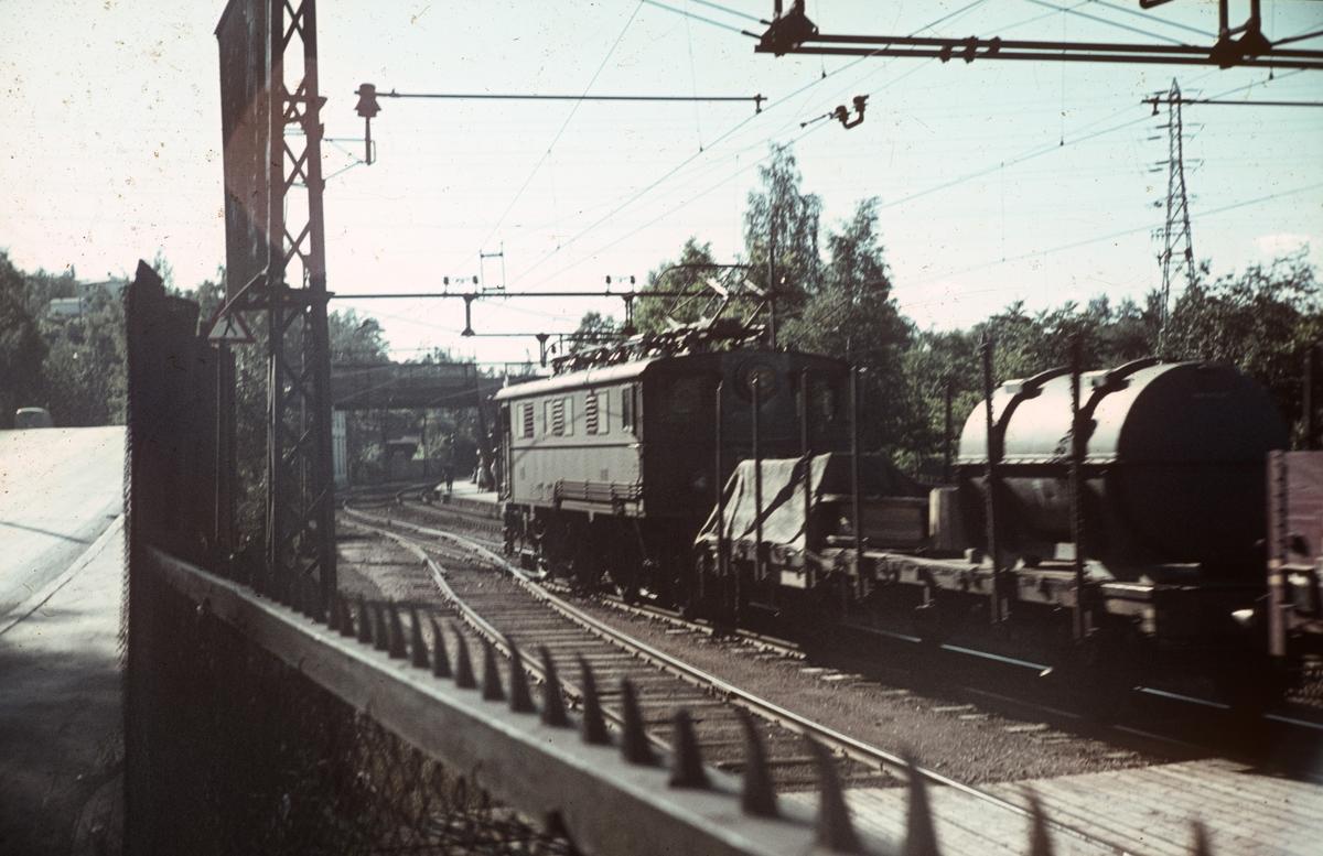 Godstog ved Bryn stasjon på Hovedbanen. Toget trekkes av elektrisk lok type El 5.