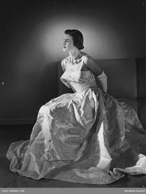 Modell i paisley-mönstrad aftonklänning, vita handskar och halsband. Höst.