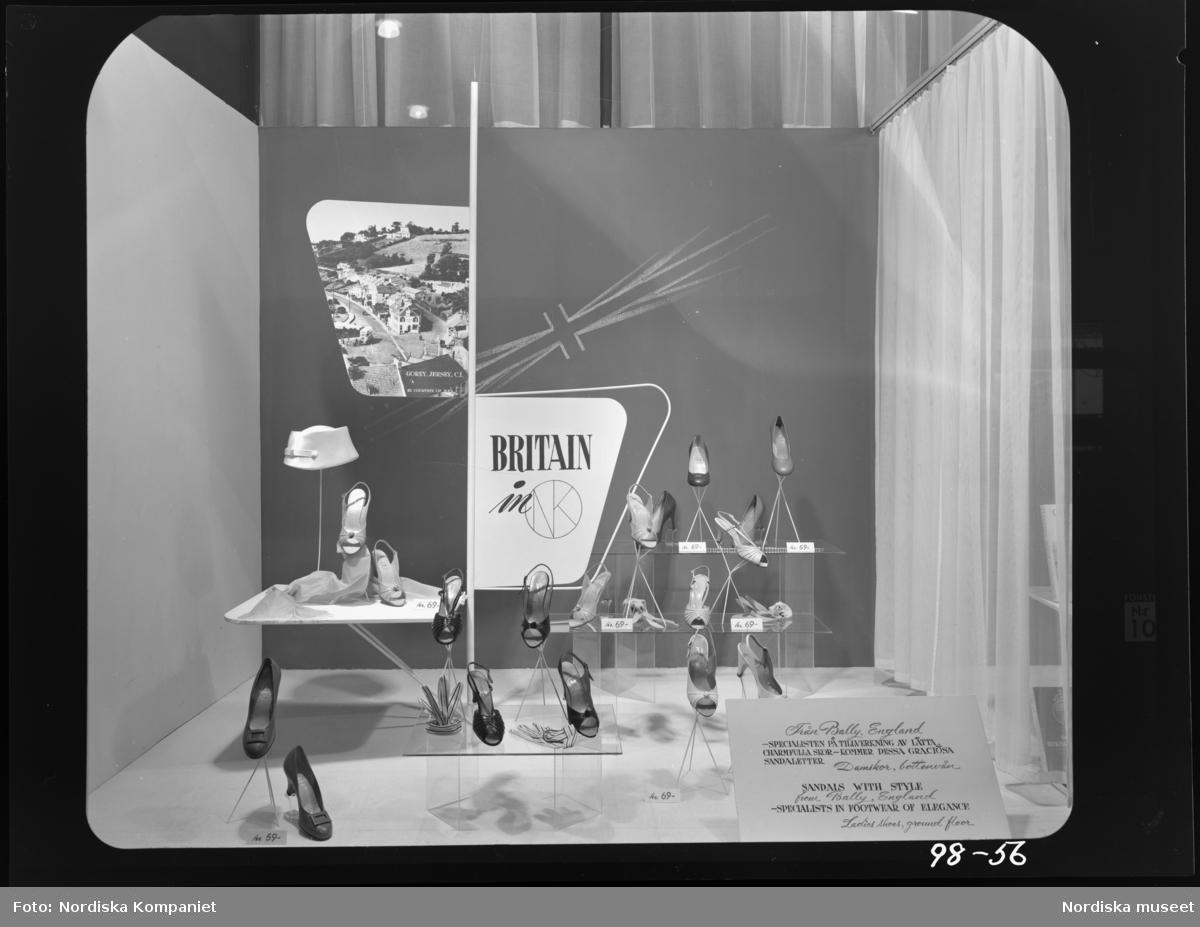 """Skyltfönster på Nordiska Kompaniet. """"Britain in NK"""" Sandaletter, klackskor och accessoarer från Bally. """"Från Bally i England, - specialisten på tillverkning av lätta, charmfulla skor - kommer dessa graciösa sandaletter"""". Foto från Gorey, Jersey CI."""