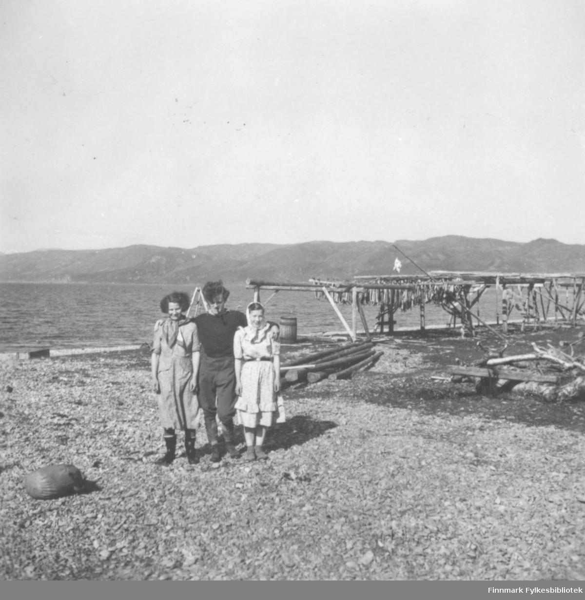 Den engelske antropologen Robert Paine som står imellom to kvinner. Ragnhild Andersen står til venstre. Kvinnen til høyre er Elbjørg Amundsen. Ned mot sjøen henger det fisk på hjeller. Fjellene ses i bakgrunnen