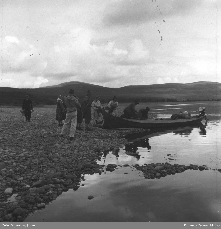 Elvebåt dratt halveis på land . En gruppe mennesker stiger opp på båten. På enden av båten  ryggsekker,  bagasje og last.