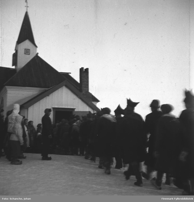 Kirkesøndag med bryllup i Karasjok kirke påsken -48.  Brudeparet, Berit Kristine Samuelsdatter Balto og Kåre Karlsen Rudsether,  med slekt og gjester marsjerer to og to i rekka mot kirka.  På dette bildet er de i ferd med å gå inn i kirka. Folk står ved døråpningen og ser på følget.