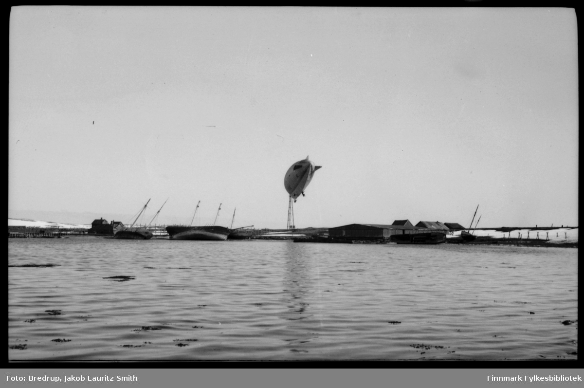 Antakelig er dette luftskipet Norge forankret i luftskipsmasta på Vadsøya, mai 1926. Man kan ikke lese navnet på luftskipet, men det var mye snø i mai dette året, og det vises på dette bildet. Bildet er tatt fra sundet mellom fastlandet og Vadsøya, og viser tydelig de russiske skipsvrakene som ligger i strandkanten på øysiden.  Man ser også noen bygninger på Vadsøya.