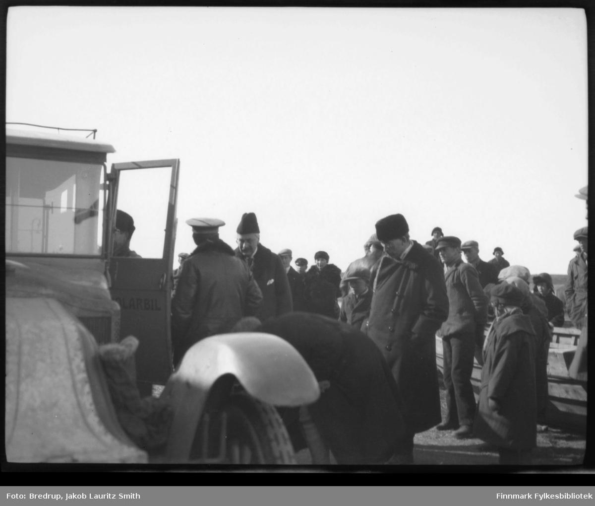 Umberto Nobile (med ryggen til) i ferd med å stige inn i en bil merket Polarbil i mai 1926.  En person er halvveis inne i bilen, Nobile snakker med et par herrer i hatt og lange frakker. En av dem kan være fylkesmann Hagbart Lund (til venstre med hvitt lommetørkle i frakkelommen). Rundt følget er det et yrende folkeliv. Bildet er tatt under luftskipet Norges mellomlanding i Vadsø. Nobile er antakelig på vei tilbake til luftskipet etter den offisielle lunsjen som ble holdt for luftskipets offiserer av fylkesmann Lund.  Personen til høyre for Lund er antakelig prost Beronka, som var tolk for det italienske følget.  Siden bilen er med på bildet, tror vi dette er tatt på fastlandet.  Og det ser mer ut som en avskjed enn en velkomst. Polarbil var et rutebilselskap etablert i 1920. Selskapet drev rutetrafikk i Øst-Finnmark. 1. januar 1976 ble selskapet overtatt av Finnmark Fylkesrederi og Ruteselskap (FFR). Rutebilen er en Renault; karakteristisk med det merkelige panseret og radiatoren bak motoren. Den hadde registreringsnummer Y-103. Rutebilen står omtalt i Bilboken for Norge 1922, 25 og 27, siste år omregistrert til lastebil.