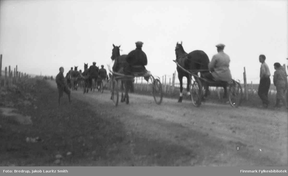 Bildet er fra travløp i Kariel september 1926.  Til høyre skimtes Karielvannet som lå midt på Karielmyra og var samlingssted for ungdom til skøyteløp og annen aktivitet.  Karielmyra ble kultivert og dermed var Karielvannet historie.  Vi ser gjerder og forgjengere som viker tilbake for hester og sulkyer som passerer.