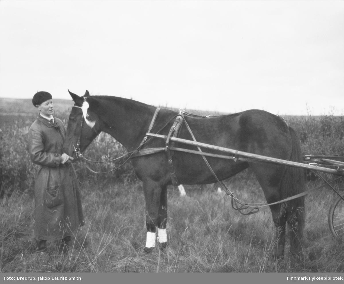 En ung kvinne i lang frakk og alpelue holder en hest forspent en sulky.  Dette er distriktslege Sigrid Skaar fra Tana med hesten 'Veslemona'.  Bildet er fra travløp i Vadsø i 1933, hvor 'Veslemona' vant sin klasse.  'Veslemona' var avkom etter fullblodshesten 'Bravo II' til kjøpmann Ole Nilsen fra Vadsø.