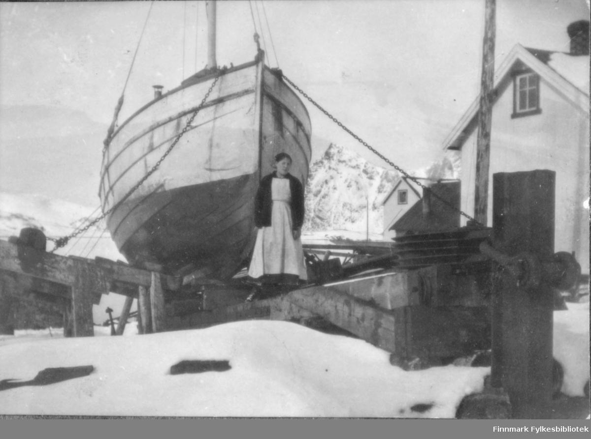 Kvinne fotografert foran båt som er dratt opp på land. Bergsfjord, ca 1915-1920?