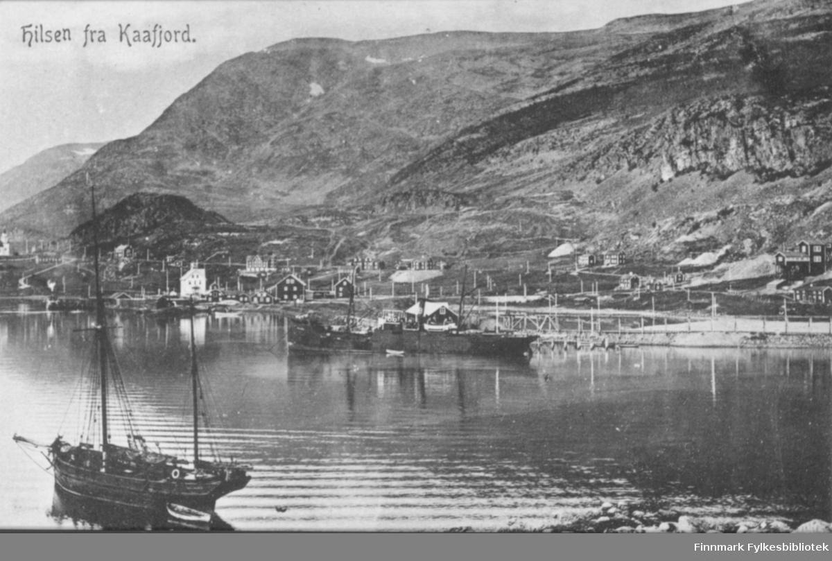 Postkort med trykt tekst 'Hilsen fra Kaafjord' - vi ser utskipningskaia til gruveanlegget og en stor lastebåt