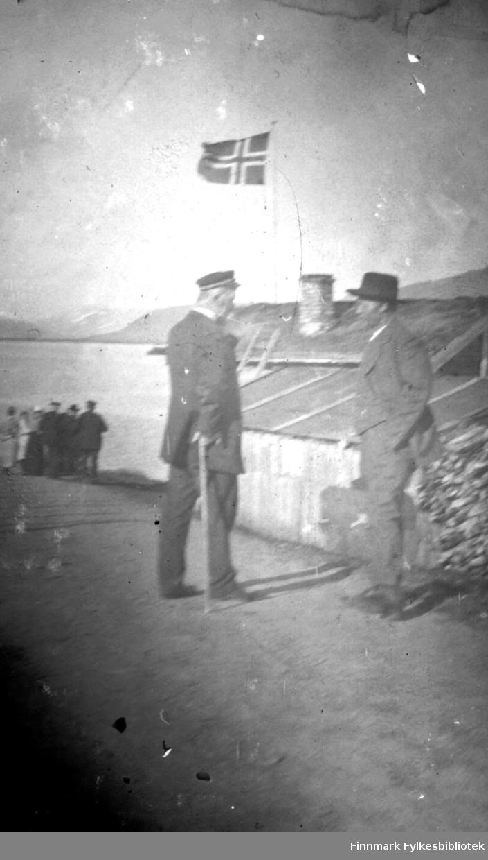To menn i passiar på Langnes foran et lite hus med flagg. I bakgrunnen en gruppe mennesker. Mannen til venstre på bildet var lensmann i Tana fra år 1900 til 1935. Han hette Johan Kristian Mostrøm Bertheussen. Var født i Vardø i 1864