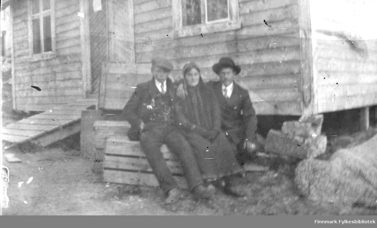 To menn og en dame sitter på en kasse utenfor et hus. Antakelig Langnes, kanskje i forbindelse med Langnesmarkedet