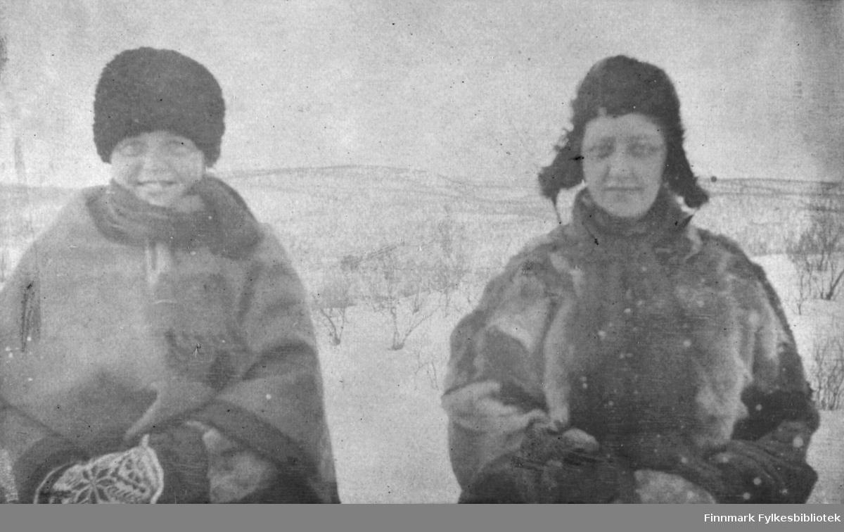 To kvinner fotografert i vinterlige omgivelser i Tana. Begge er kledd i pesk, og har både skjerf, lue og votter på