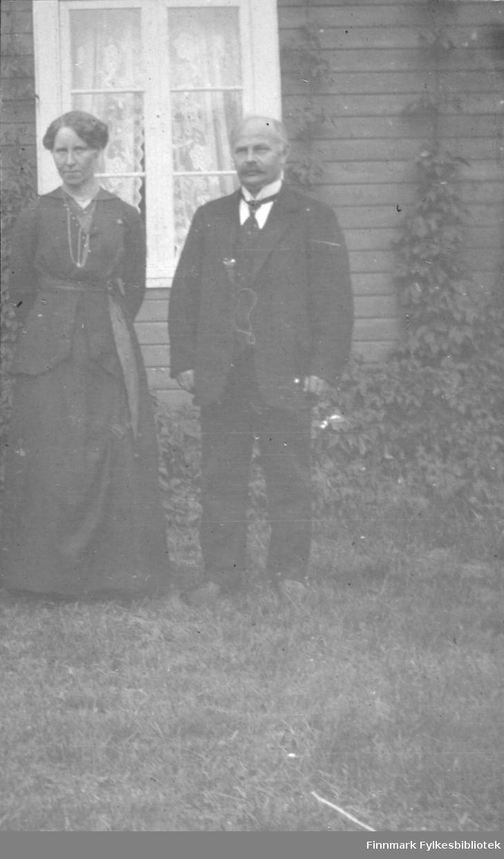 Emma og Johannes Reiersen står foran et hus i Rasjok i Tana. Begge er pyntet, han i dress og hun i kjole.