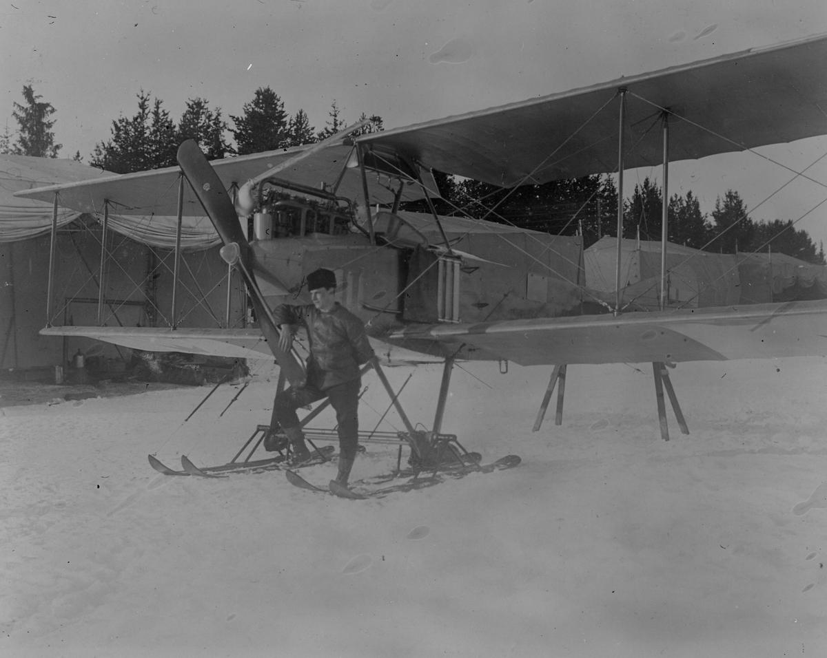 Flygplan Albatros BIIa med skidor framför tälthangarer i Boden, vintertid, 1916. En man står vid propellern.