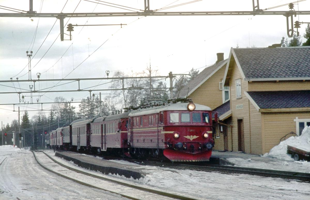 Persontog 207 Oslo Ø - Gjøvik passerer Sandermosen stasjon. NSB elektrisk lokomotiv type El 11 og to motorvognsett type 65, samt en enkel personvogn bakerst. På grunn av påsken var det mangel på personvogner og det gikk derfor motorvognsett (lokaltogsmateriell) i dette toget.