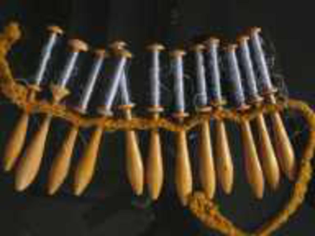 Små trådsneller m. håndtak. Alle er påviklet tråd i gråblå farge og er festet i en hullet snor til bruk på knipleputa. Er trolig brukt til et kniplearbeid og er klippet av og lagret med trådrestene i behold.