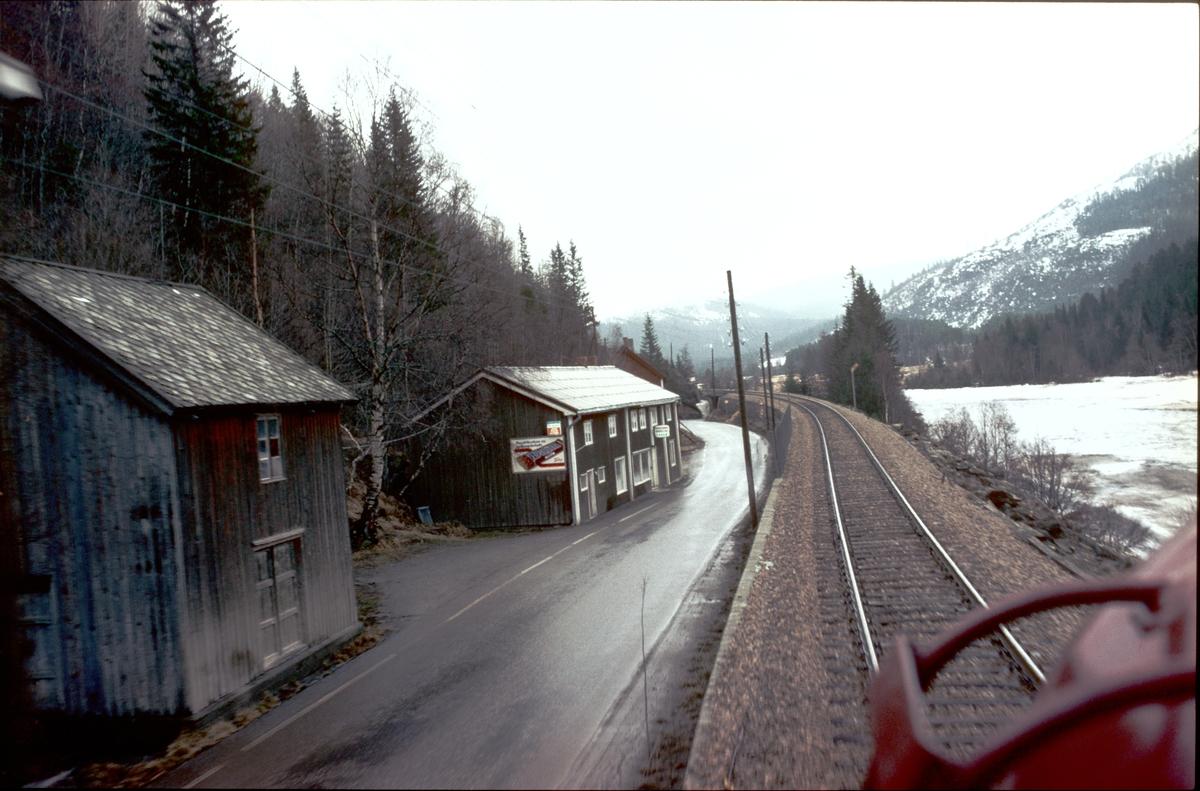 Tog 302, dagtoget Trondheim - Oslo, på vei oppover Gauldalen ved Flatberg. Her var det en landhandel som senere ble nedlagt. Riksvei 30 krysset Rørosbanen i en undergang under sporet. Riksvei 30 er lagt om her og går nå i bru over sporet.