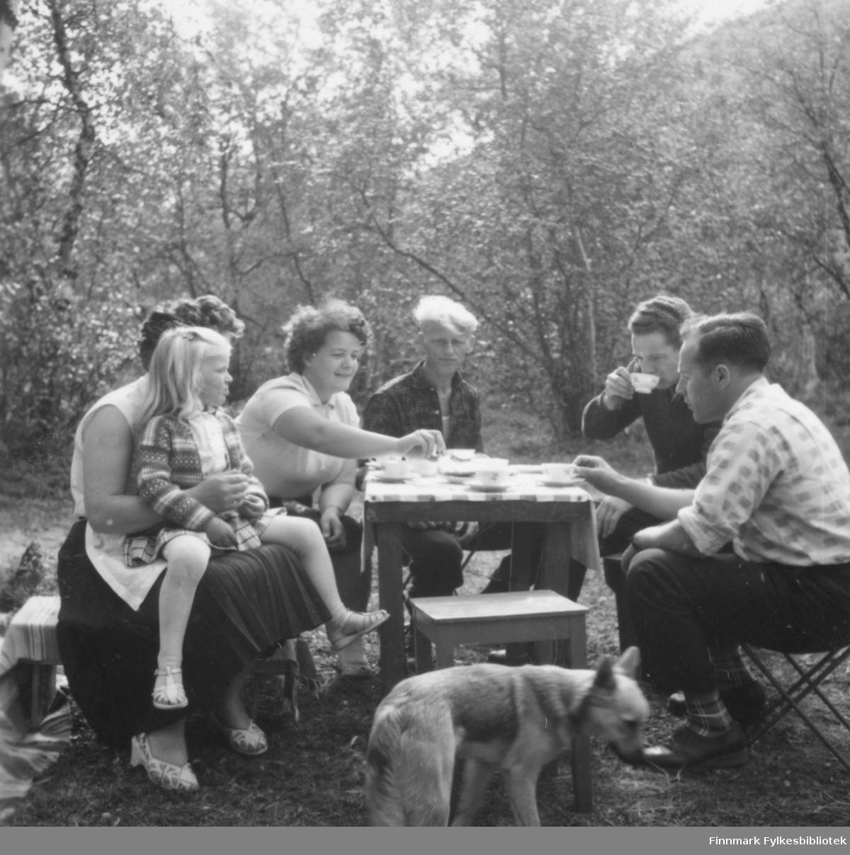 Kaffebord ute, kanskje samme hyttebesøk i Lismajok som 05046-077. Fra venstre: Ser ut til å være Anna Malinen med datteren Lise på fanget, så Ragnhild Ebeltoft, Bjarne Feldt?, ukjent, Ingvald Malinen